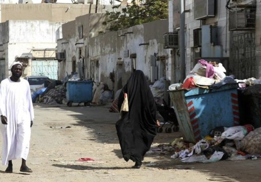 Immigrants walk along a street in the Jeddah slum of Karantina, February, 2013.