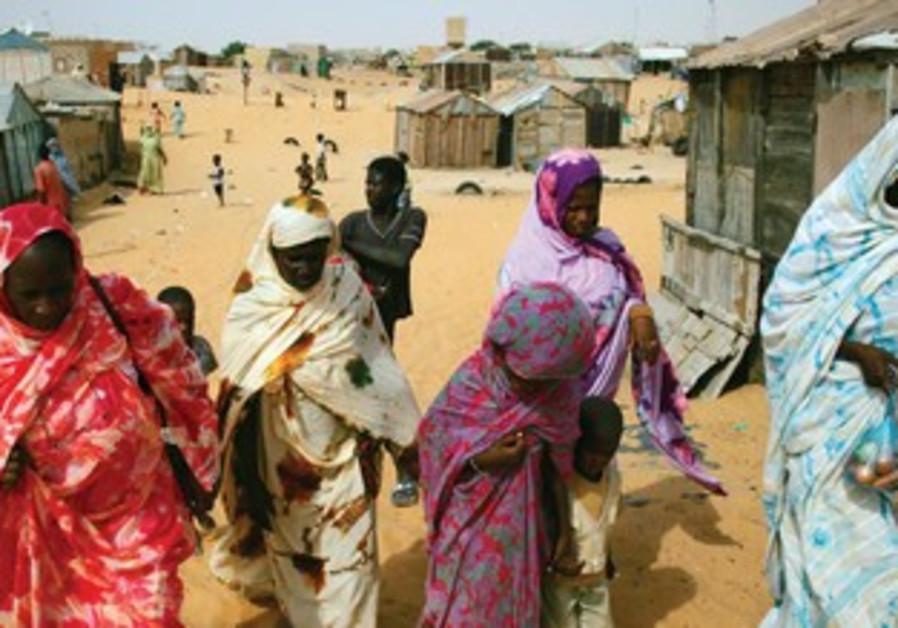 MAURITANIAN FORMER SLAVES walk in the desert outside the capital of Nouakchott.