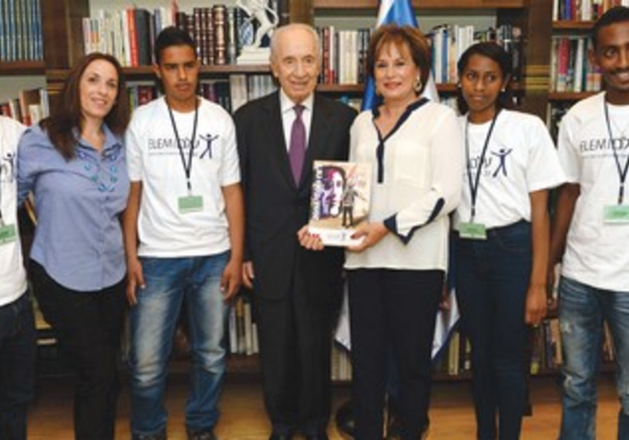PRESIDENT SHIMON PERES (center) poses with Nava Barak (on his left) and youth helped by Elem.