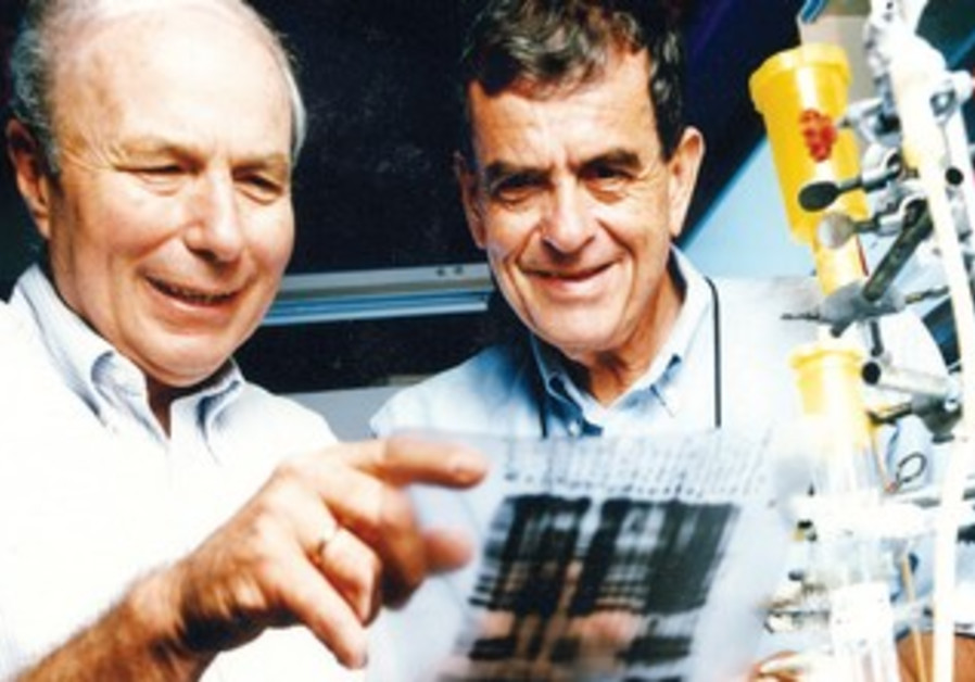 PROF. AVRAHAM HERSHKO (left) and Prof. Aharon Ciechanover examine a slide.