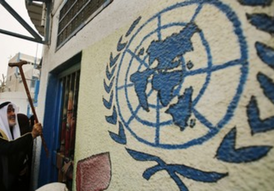 A Palestinian refugee knocks on the closed gate of the UNRWA headquarters April 8, 2013