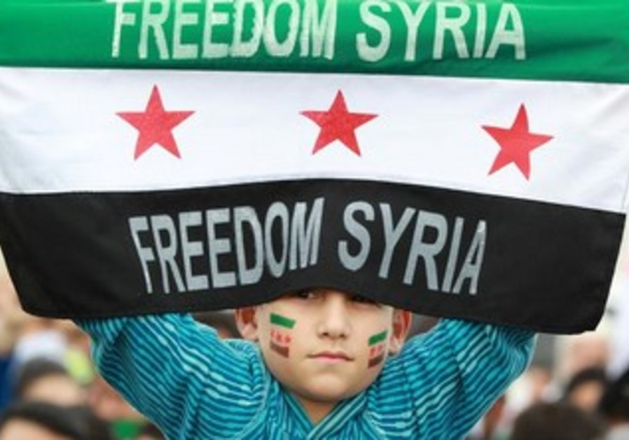 Syrian living in Jordan holds opposition flag in front of Syrian embassy in Amman March 15, 2013.