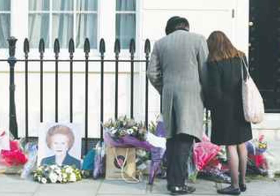 PEOPLE GAZE at memorabilia left outside 10 Downing Street commemorating Margaret Thatcher