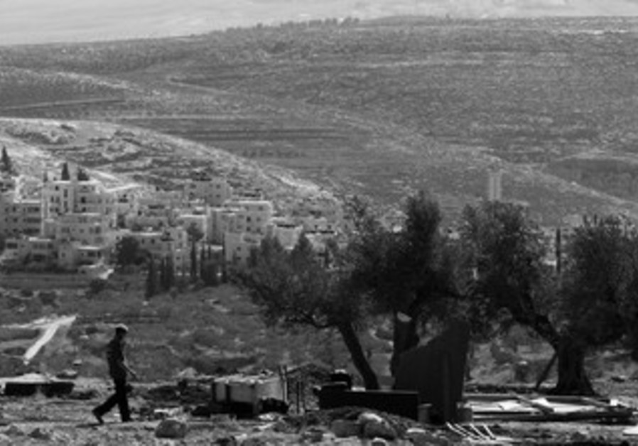 A JEWISH man walks on a hilltop overlooking a suburb of Ramallah.