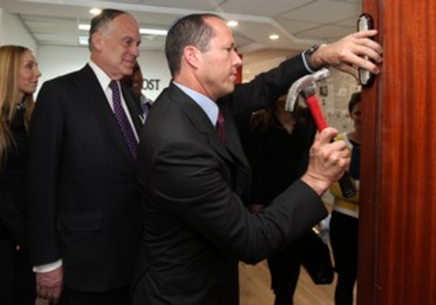 Jerusalem Mayor Nir Barakat affixes mezuza at Jerusalem Post offices, April 2013.