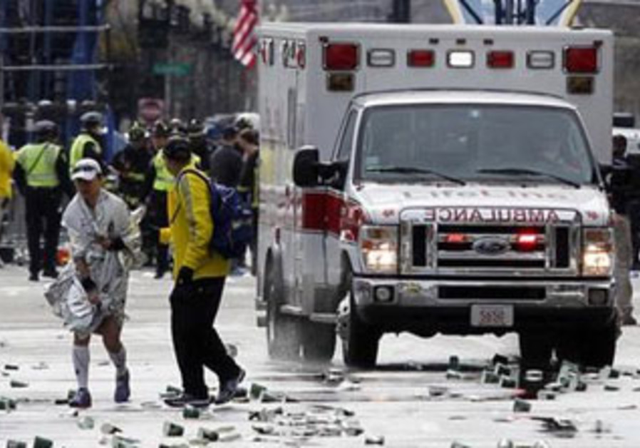 A runner is escorted from the scene after two explosions at the Boston marathon, April 15, 2013.