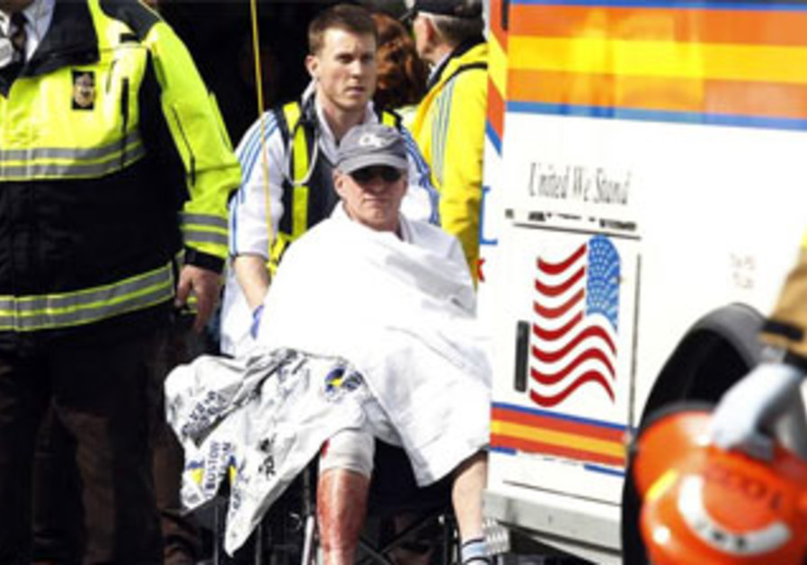 A runner is wheeled from a triage tent after twin blasts at the Boston Marathon, April 15, 2013.