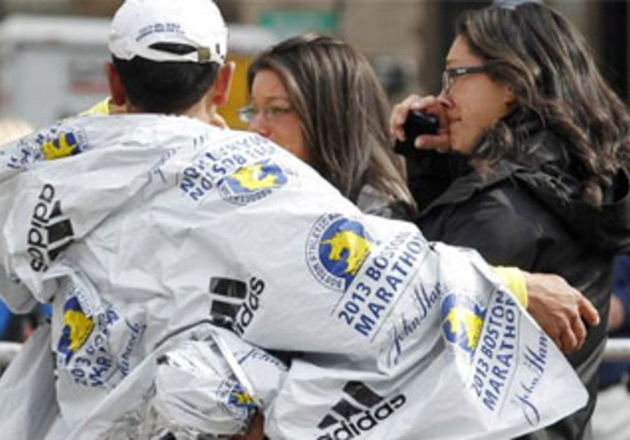 People comfort each other after deadly twin blasts at the Boston Marathon, April 15, 2013.