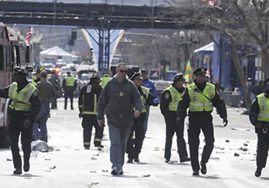Public safety officials evacuate the scene after twin blasts at the Boston Marathon, April 15, 2013.