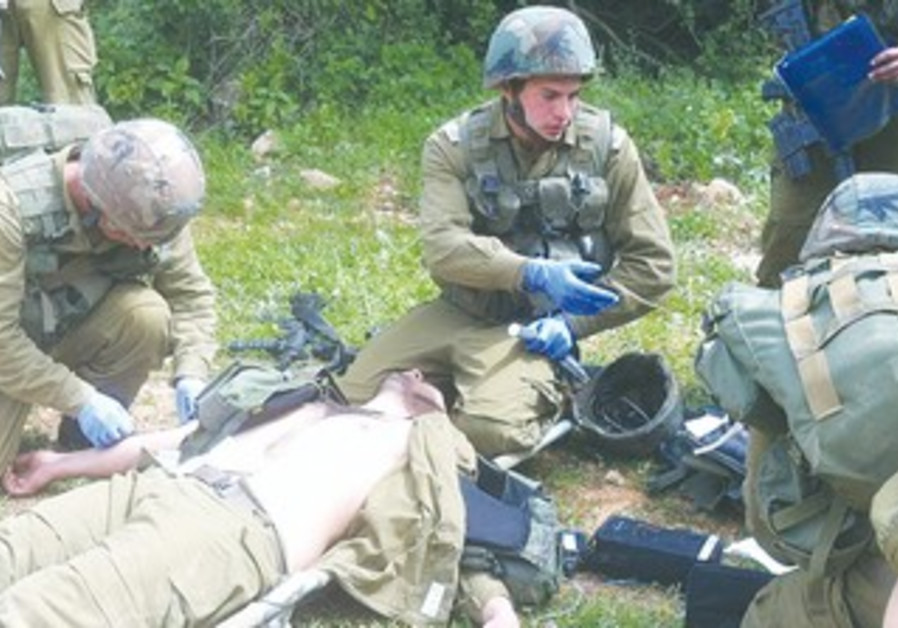 LT. GILAD SPIEGEL (center) treats a soldier in the field.