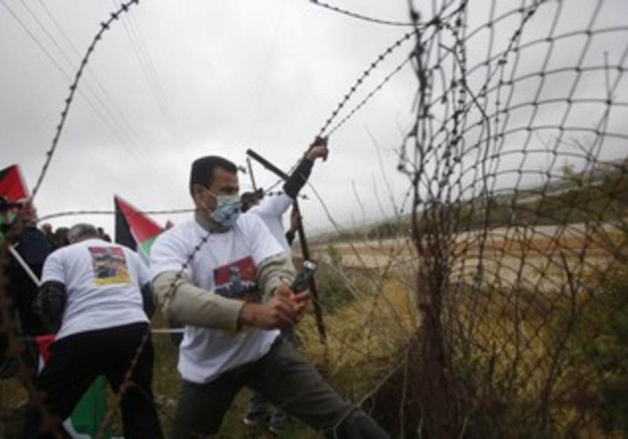 Palestinian activists cut a part of a fence near Israel's Ofer military prison and the West Bank cit
