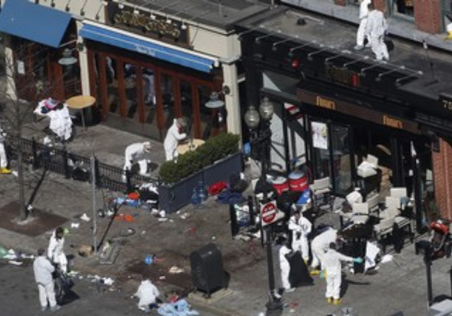 Officials take crime scene photos two days after two explosions hit the Boston Marathon, April 17