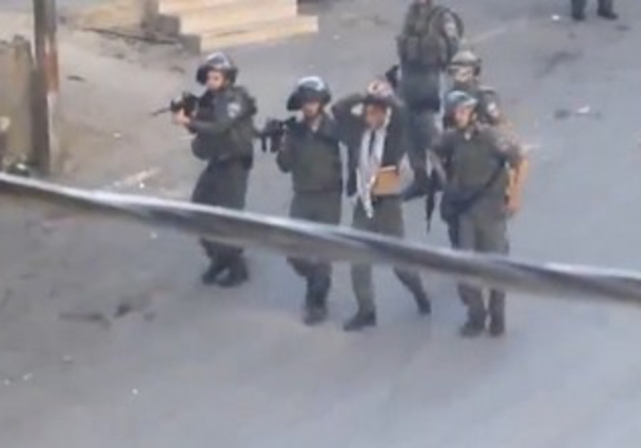 Officers with bound Palestinian teen