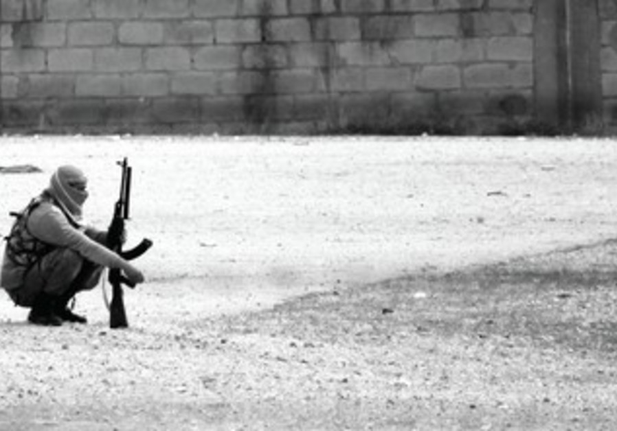 A FREE Syrian Army fighter listening to fighting in a northern Syrian Kurdish town.