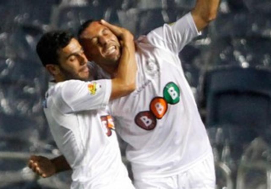 MACCABI NETANYA striker Ahmed Saba (right) is embraced by teammate Yossi Shivhon.