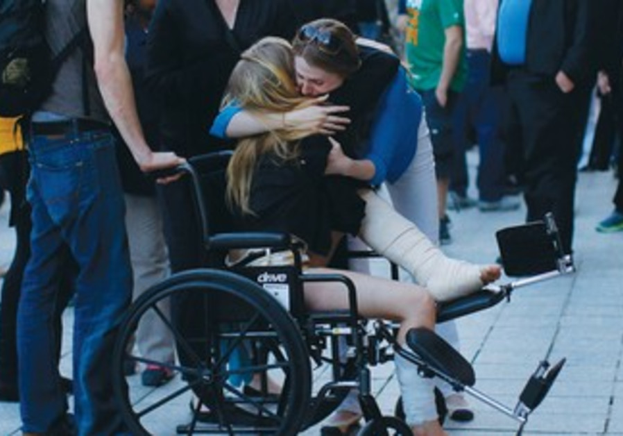 A WOMAN wounded by the Boston bombing sits in a wheelchair on the sidewalk in Boston.