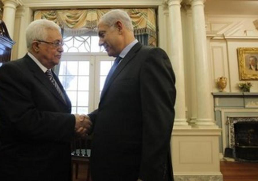 Prime Minister Benjamin Netanyahu (R) greets Palestinian President Mahmoud Abbas