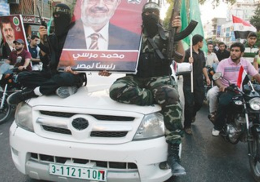 HAMAS GUNMEN hold a poster depicting Mohamed Morsi of the Muslim Brotherhood in Gaza City June 2012.