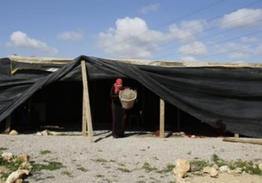 A woman carries produce in the Tel Sheva settlement near Beersheva