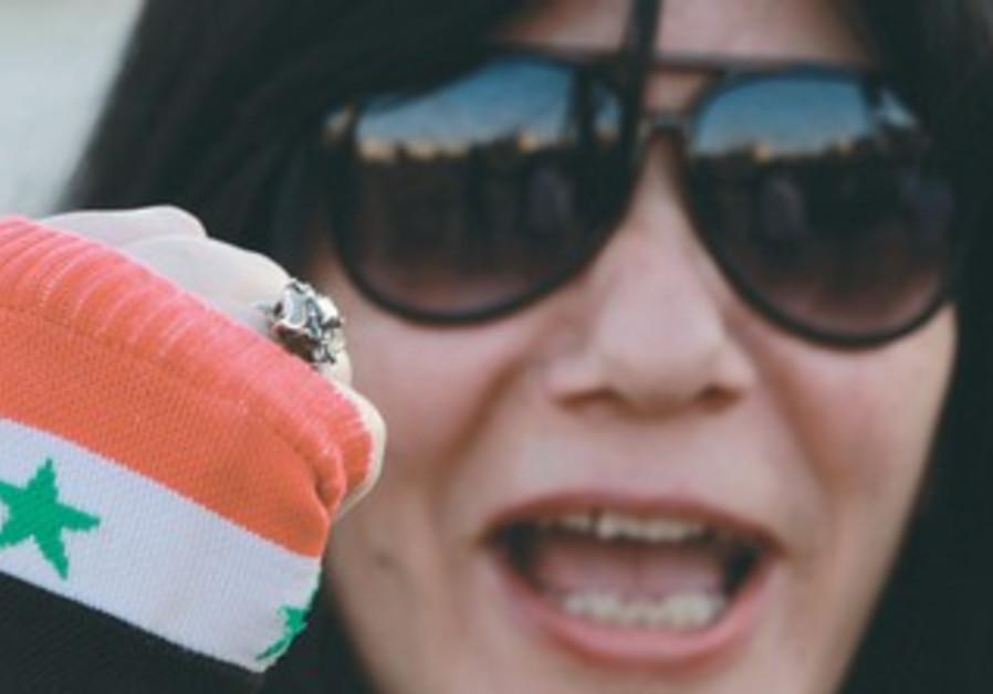 JORDANIAN ACTIVIST wearing a glove with the colors of the Syrian flag protests against Israel.