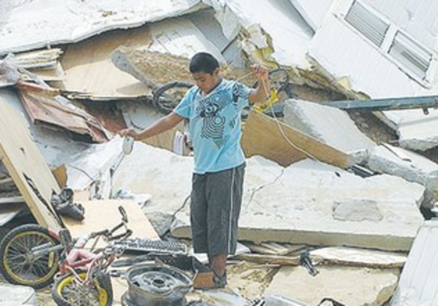 Beduin boy stands on rubble of demolished house in Arakib in 2010.