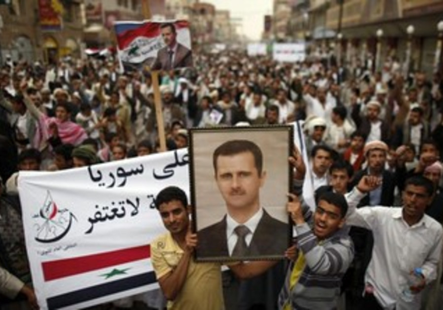 Anti-government protesters hold up a picture of Assad.