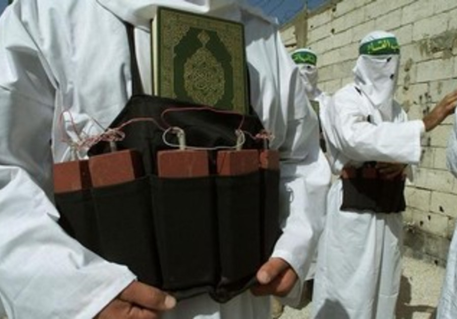 A man wears a simulated suicide belt with a Koran tucked in.