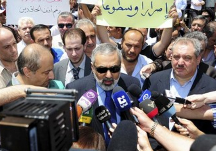 Syrian Information Minister Omran al-Zoubi (C) as Zoubi speaks to members of the media at Syrian TV.