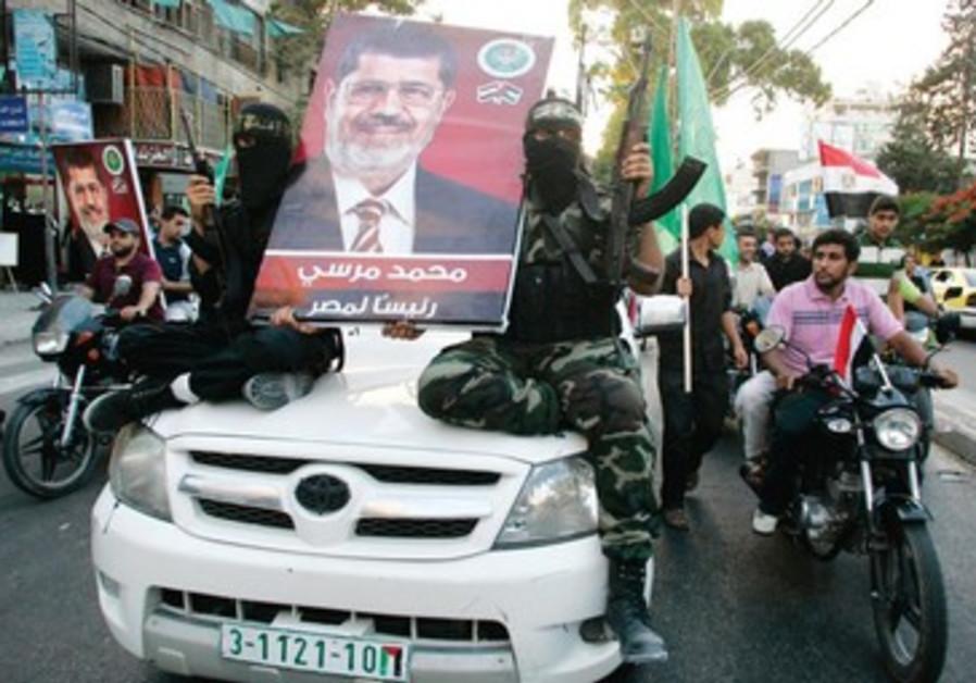 Des hommes armés du Hamas brandissent un poster de Morsi fraichement élu président à Gaza.