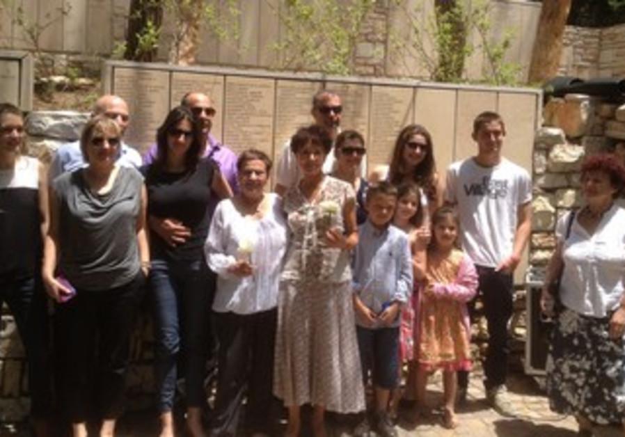 KAROLINA EISEN (center, holding white rose), poses with her family Monday.
