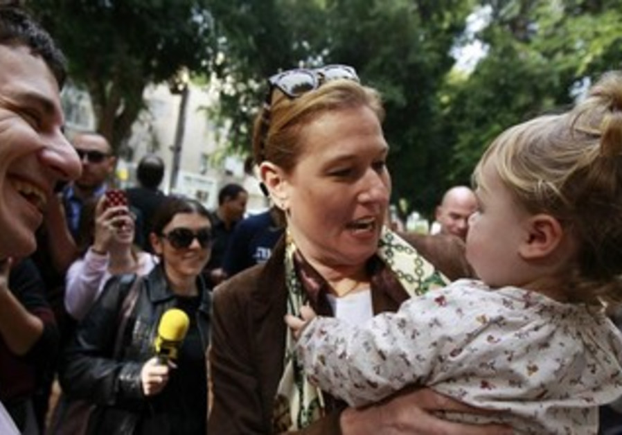 Tzipi Livni holding a young girl.