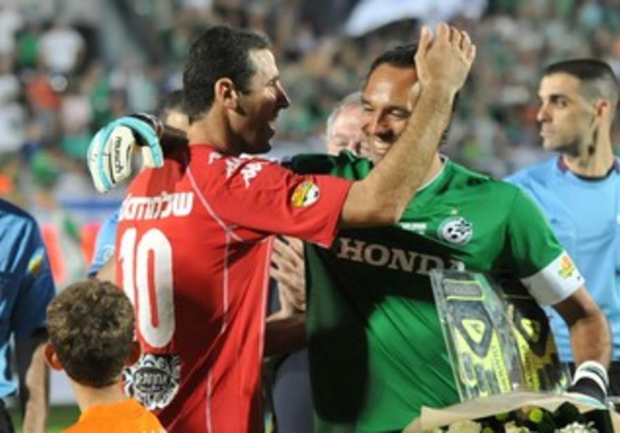 MACCABI HAIFA goalkeeper Nir Davidovich (right) and Hapoel Tel Aviv defender Walid Badier embrace