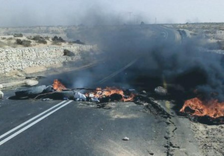 CAR TIRES set alight by masked Beduin burn on Negev highway