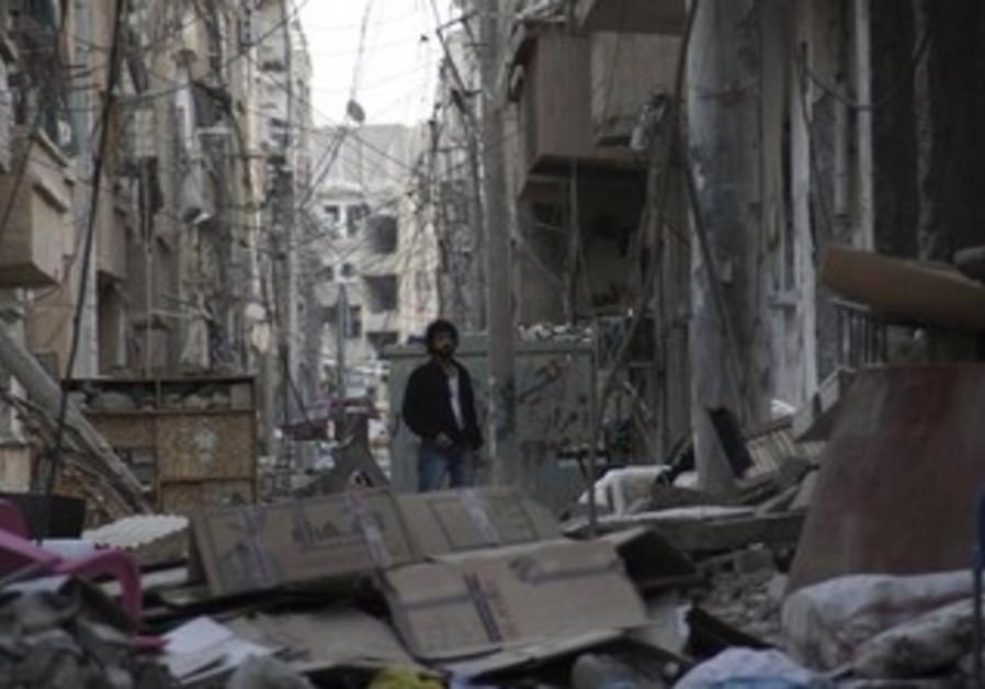 Man stands in rubble in Deir al-Zor, May 19, 2013.