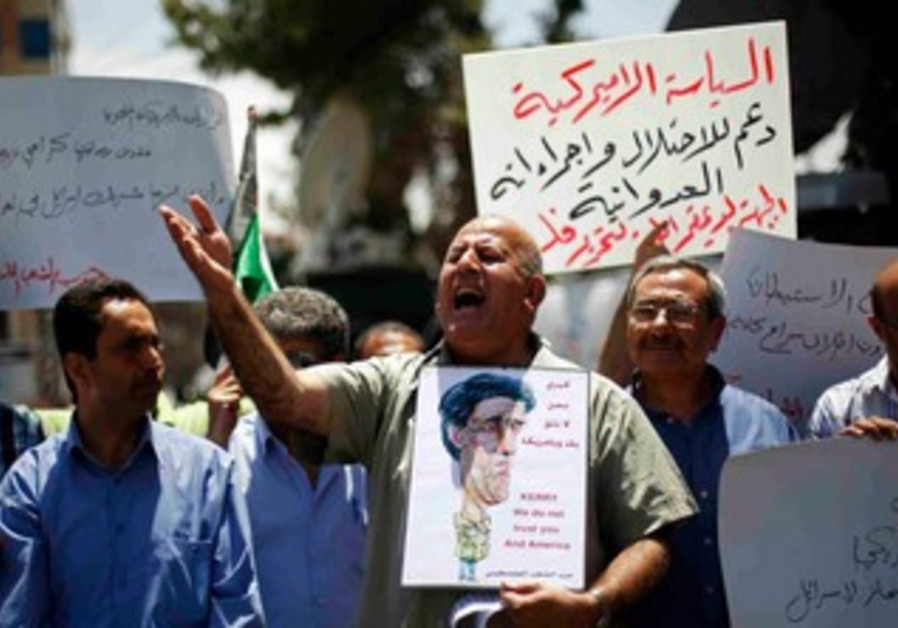 Palestinian protester holds a poster with a caricature of John Kerry in Ramallah May 23, 2013.