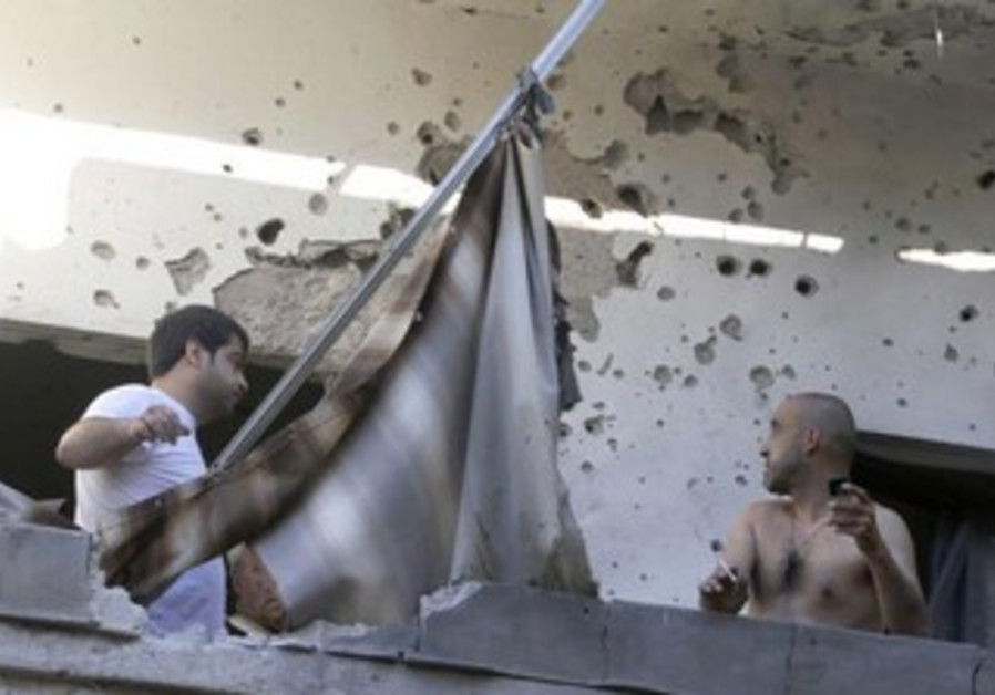 Two men inspect their house damaged by rockets in Beirut  suburbs May 26, 2013