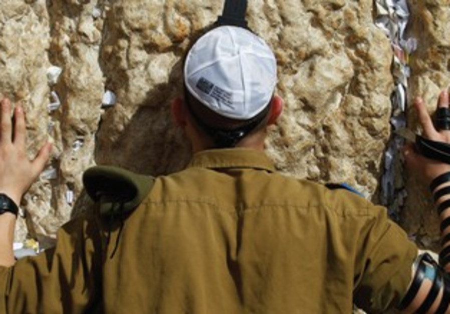 A soldier prays at the Western Wall. '