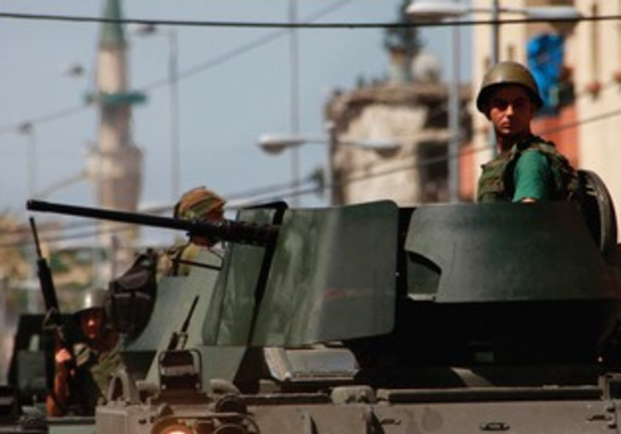 LEBANESE ARMY soldiers ride on their military vehicles in the port city of Tripoli, northern Lebanon