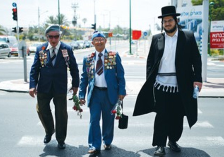 AN ULTRA-ORTHODOX man walks past two veterans of the Second World War in Ashkelon.
