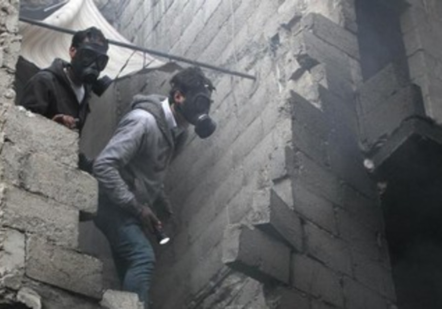 Residents wear masks after shelling by forces loyal to Assad in Aleppo January 3, 2013.