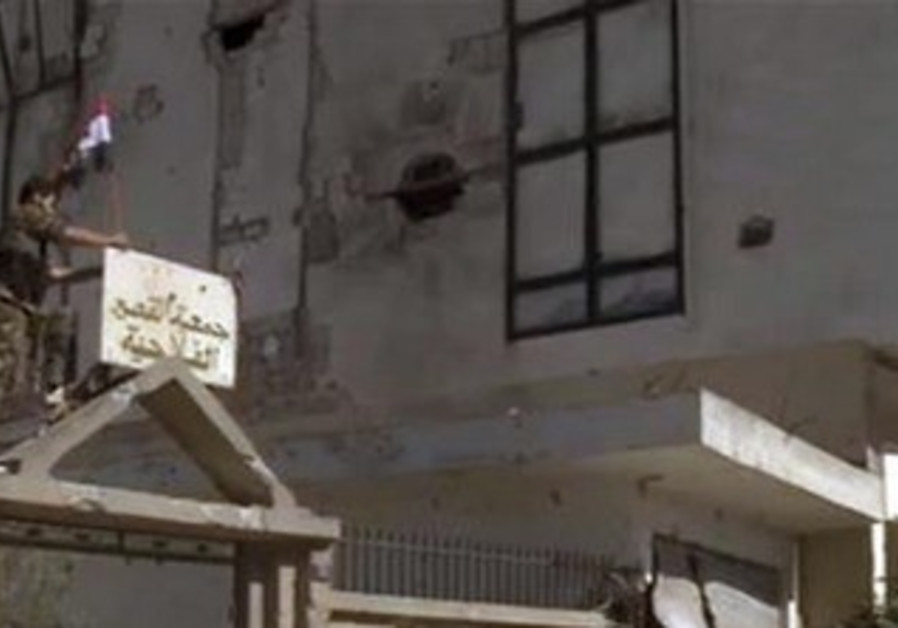 A member of forces loyal to Syrian President ssad erects a Syrian flag atop of a gate in Qusair.