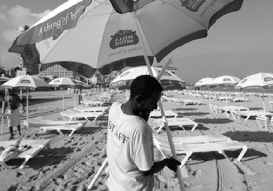 AN ERITREAN migrant worker placed umbrellas on a beach in Tel Aviv.