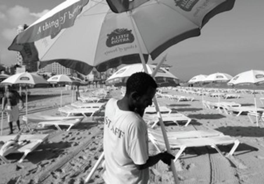 AN ERITREAN migrant worker placed umbrellas on a beach in Tel Aviv.