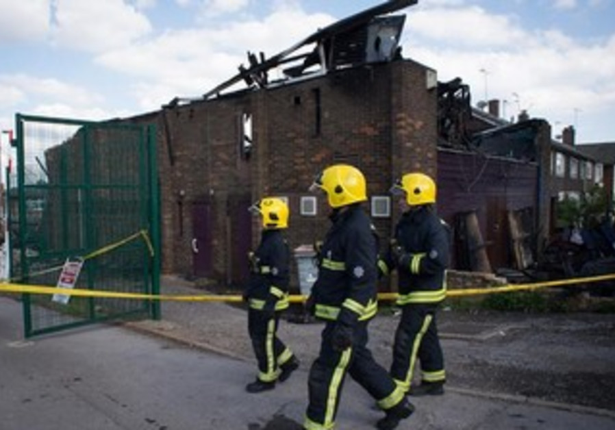 Firefighters walk past the Al-Rahma Islamic Centre that was damaged by fire, in north London June 5