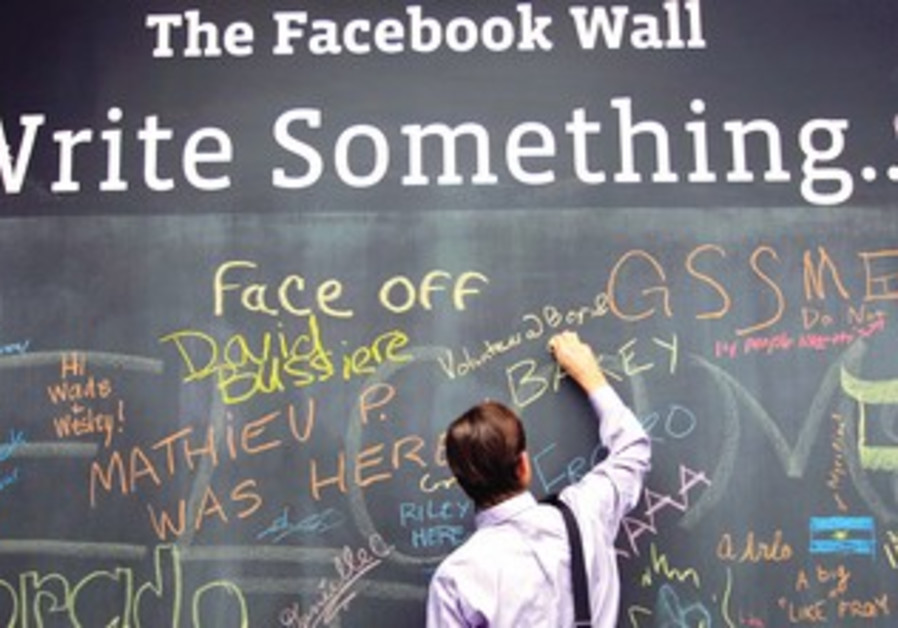 AN EMPLOYEE adds his message to a wall at the Facebook headquarters in Menlo Park, California.
