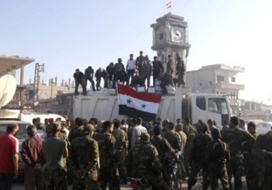 Soldiers loyal to the Syrian gather in Qusair, after Syrian army took control of the city, June 5.