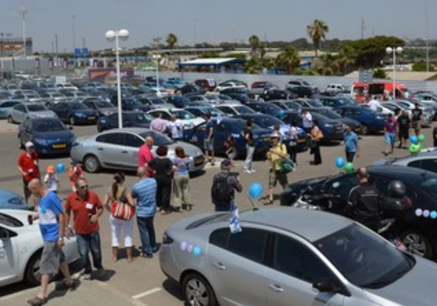 Supporters rally for electric car use.