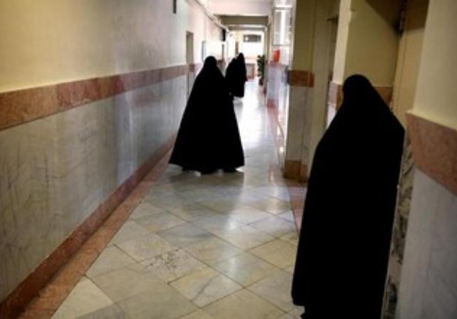 Female prison guards walk along a corridor in Tehran's Evin prison June 13, 2006.