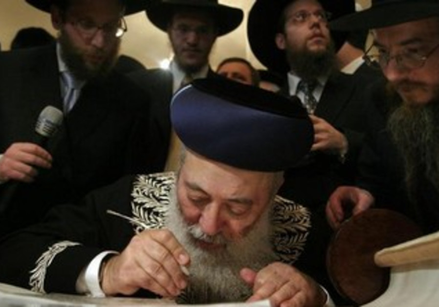 Israel's chief rabbi Shlomo Amar writing in a Torah scroll.