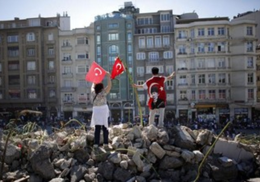 Protesters wave Turkish flags during a demonstration at Gezi park near Taksim Square in Istanbul